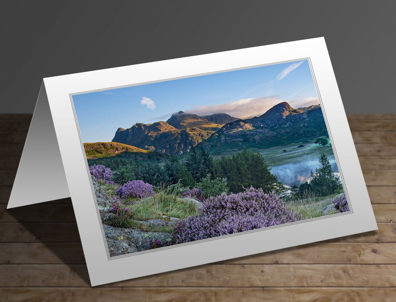 A greetings card containing the image Heather surrounds a misty Blea Tarn and the Langdales