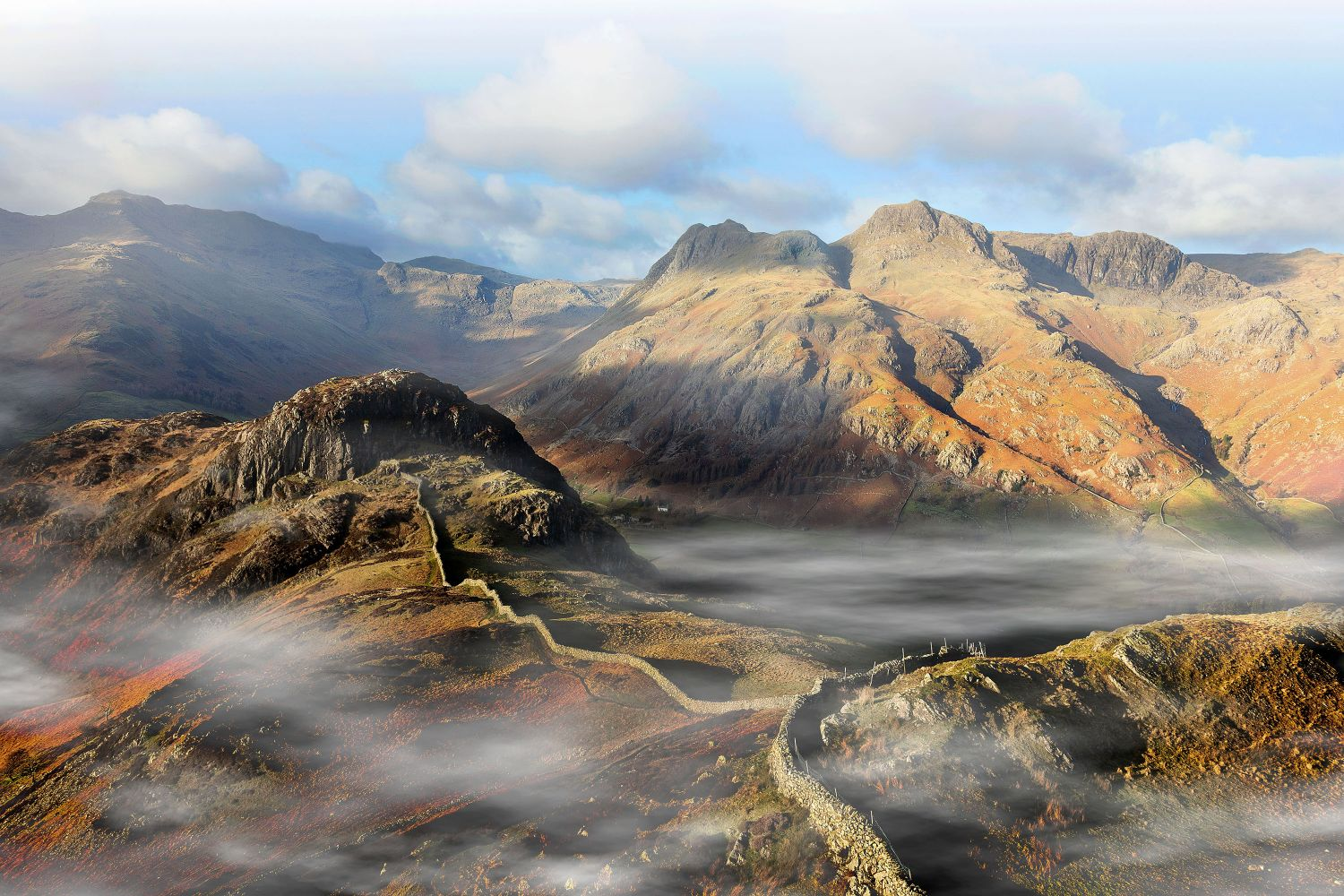 Early morning mists surrounds the Langdale Pikes by Martin Lawrence