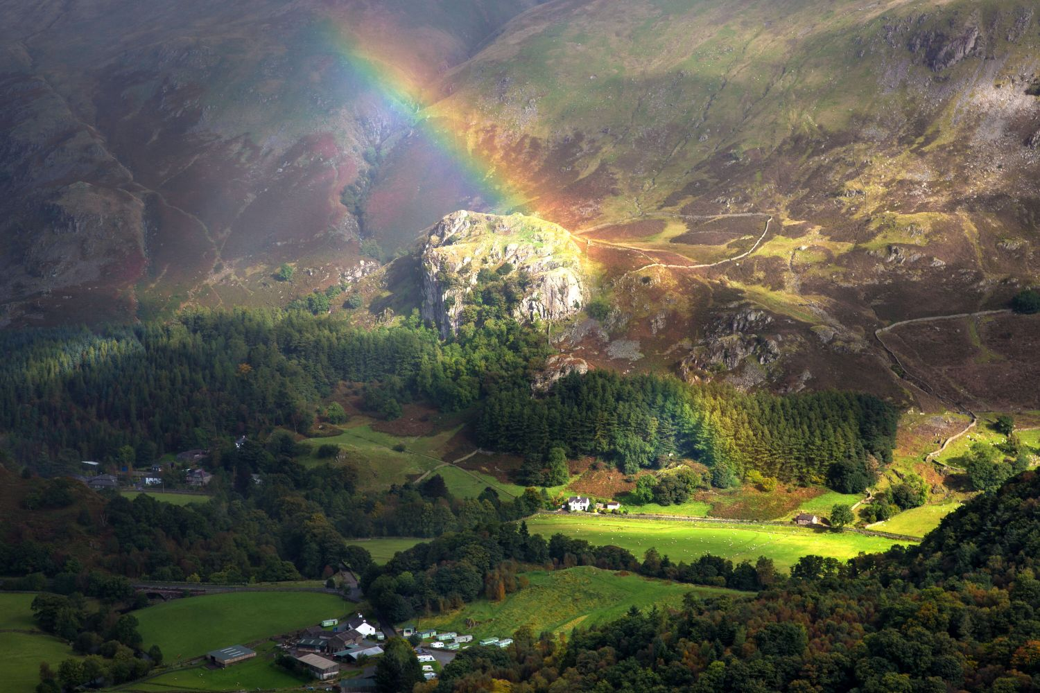 A beautiful rainbow ends over Castle Rock of Triermain in St Johns in the Vale in the English Lake District