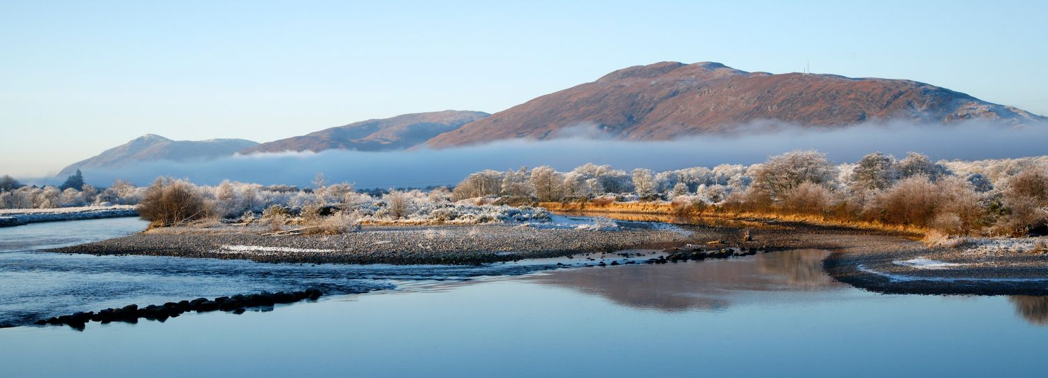 River Lochy from Inverlochy Castle with low lying mist over frost covered trees