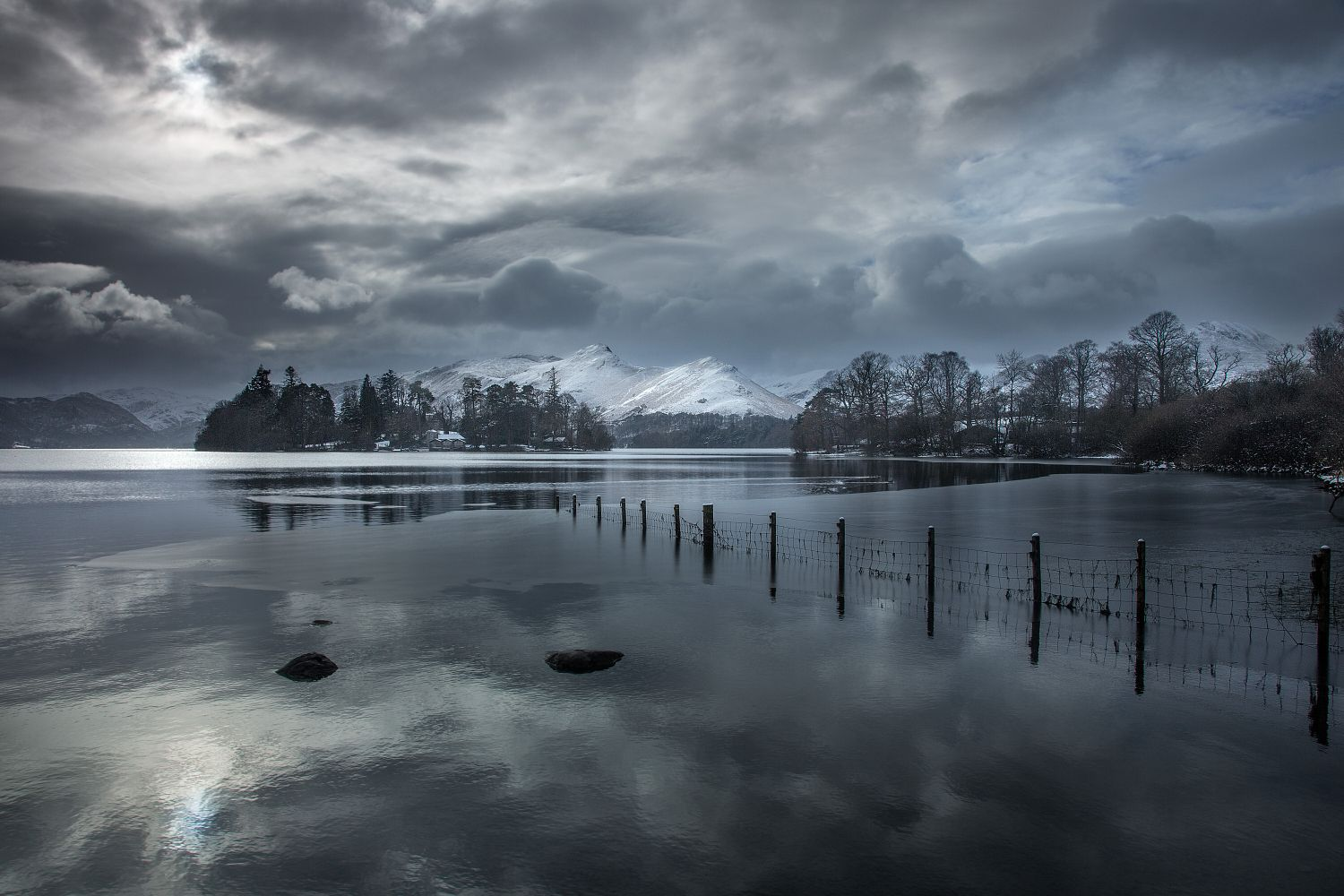 A snow-covered Catbells seen cross Derwentwater bathed in shafts of light