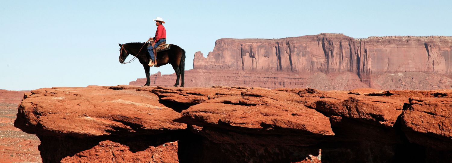 A panoramic image of John Ford Point, Monument Valley with a Navajo Indian on Horseback