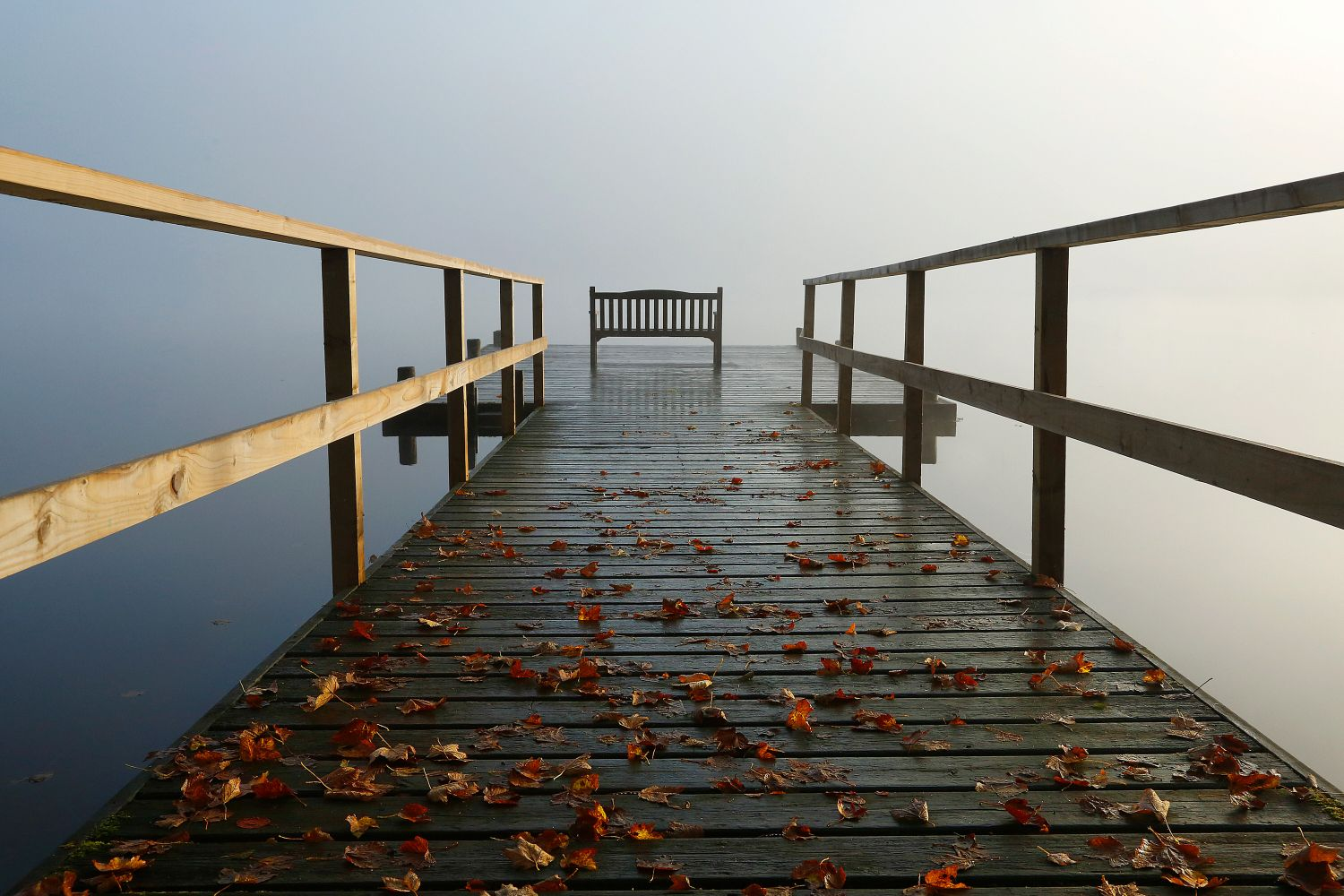 An autumn shot of the jetty at Pullwood Bay on the shores of Windermere in the English Lake District